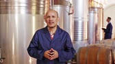 отсек : Portrait of a mature male cheerful worker standing on a wine factory in fermentation
