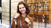 кулон : Cheerful young woman selling different pendants and bracelets in the market Стоковые видеозаписи