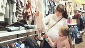 pregnant mother and small daughter choosing clothes for baby in children cloths shop