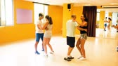 step : Smiling adults dancing salsa together in dance studio Stock Footage