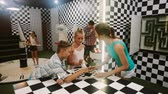 questões : Young family is visiting of escaperoom stylized under chessboard. Stock Footage