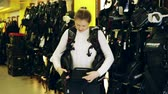 выборе : Sporty woman is trying new diving vest in the diving store. Стоковые видеозаписи