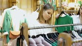 cabide : Positive young women friends choosing green pullover in the fashion store Stock Footage
