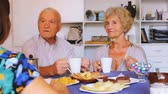 gastos : Happy senior couple enjoying conversation with female over coffee at home