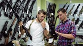 airsoft : positive young men in the military shop Stock Footage