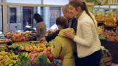 cart n corrugado : Portrait of friendly family of three with shopping cart full of fruits and vegetables in greengrocery