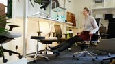 memnun : Satisfied young woman sitting in the ergonomic office chair in the store before buying
