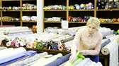 exposto : Portrait of an attractive girl choosing a fabric among the variety on the shelves in the store