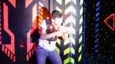 arma curta : Modern young people playing laser tag on dark labyrinth in bright beams of laser pistols