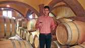 titular : Male owner of winery standing with wine in cellar