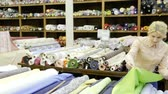exposto : Young woman looking for interesting cloth in textile shop