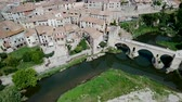 načervenalý : View from drone of medieval Spain town of Besalu with Romanesque bridge over Fluvia river