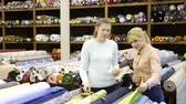 Polite female seller helping young woman in choice of interesting cloth in textile shop Stock Footage