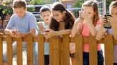Children are playing on a smartphone in the playground.