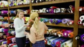 exposto : Smiling young women shopping together in textile shop, choosing textiles for dressmaking