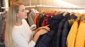 cardigan sweater : Cheerful blonde girl standing in boutique and choosing kids clothes Stock Footage