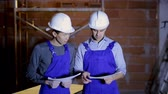reconstruction : Asian and Hispanic workers holding blueprints of building