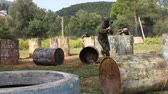 Paintball players aiming and shooting with guns at opposing team outdoors Stock Footage