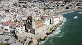 taşra : Aerial view of Sitges small town with church on Mediterranean coastline, Spain Stok Video