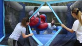 materac : Laughing African American man in big boxing gloves having fun on inflatable ring on adults bouncy playground Wideo