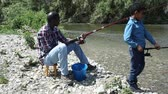 decoy : Positive African man and little boy standing near river and fishing with rods Stock Footage