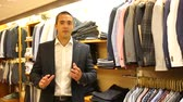 prodavač : Successful male administrator of men clothing store demonstrating large assortment of garments