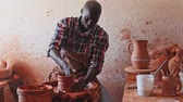shaping : Talented young African potter at his own pottery studio working on new unique items