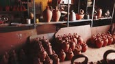 capacidad : Clay jugs and utensils on racks in store