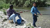 decoy : Portrait of cheerful afro man and his little son fishing with rods on river Stock Footage