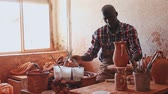 shaping : Focused African guy working in pottery workshop, painting ceramic jug he created