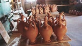 cruche : Various handmade utensils from baked clay on floor and on racks in pottery workshop Vidéos Libres De Droits