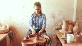Female artisan in ceramics workshop with pottery wheel and various clay vessels