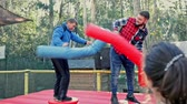 Happy male friends fighting by big stuffed boxing gloves at outdoor amusement playground 影像素材