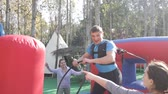 Emotional man tied with rope to his friend competing to collect hoops on inflatable ring 影像素材