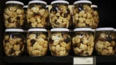Closed glass jars with popular in Catalonia pickled young fredolics (tricholoma terreum mushrooms) on shelf in store 影像素材