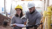 Female architect and young contractor discussing construction plan at building site