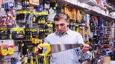 Confident man is choosing bucksaw in tools store 影像素材