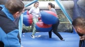 inflável : Friends having fun in outdoor amusement park,  two men watching women in big boxing gloves boxing on inflatable ring