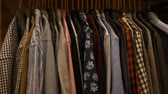 verificador : Large assortment of shirts displayed on clothing rack in men clothes shop
