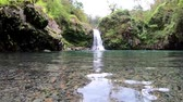 ハワイ : From the water level looking across the lagoon at a beautiful waterfall in Maui Hawaii