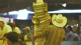 terceiro : Man walking through a busy outdoor market in Mexico carrying a large stack of cowboy hats. Vídeos