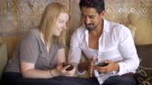 flirting : A young attractive couple each surf on their cell phones mobile devices and share with each other, lovingly, what theyve been looking at. Dolly shot against a modern home and comfortable sofa. Stock Footage