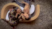 arrelia : Overhead dolly shot of 2 dancers, a Mexican man and Japanese women in a traditional geisha outfit, flirting and pleading with his partner to pay attention to him on a curved serpentine chair.