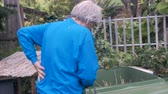 painéis : Hand held of an elderly man rubbing his back while working in the yard. It appears that he is experiencing back pain Stock Footage