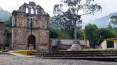 reconstrução : A wide shot of an old church and empty plaza in Antigua, Guatemala in the day. A bird lands gracefully on top of the church entrance. Stock Footage