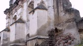reconstrução : Pan up of an ancient church in ruins in Antigua, Guatemala as a cyclist rides by this crumbling place of worship Stock Footage