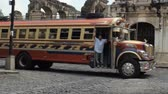 reconstrução : An old decked out school bus drives by the ruins of a church in Antigua, Guatemala. This pimped out school bus has become part of the public transportation system in this Central American Country