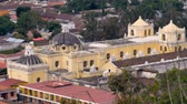 reconstrução : Establishing shot of a large yellow church shot from above in Antigua, Guatemala. You can see some of the repairs that have been done to the main dome