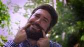 irreal : Close up portrait of a young hipster man with a full beard forcing himself to smile by touching his fingers to the sides of his mouth and moving his mouth into a smile. A real life emoticon in an outdoor setting with natural lighting and a unique expressi Stock Footage