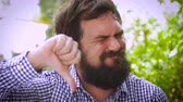 objection : Close up portrait of a young hipster man with a full beard gives a thumbs down in disgust. A real life emoticon in an outdoor setting with natural lighting and a unique expression. Stock Footage